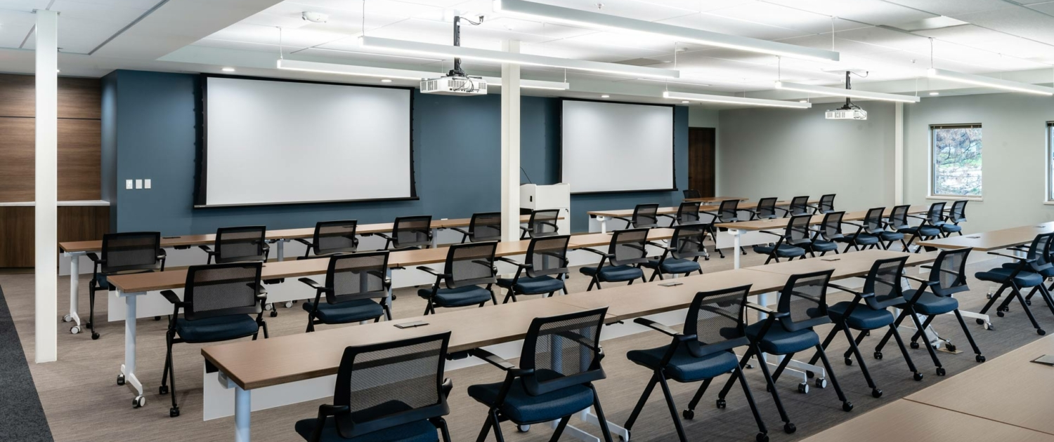 WBA Engagement Center Classroom. Chairs at rows of tables, projector screens in front
